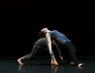 Two dancers interact, one is arching their back and leaning on the other who is crouched