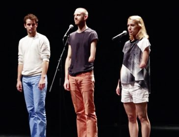 Image of three candoco dancers from Let's Talk About Dis' standing at the front of a stage about to introduce themselves