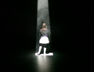 image of the back of a dancer from Anjali pictured under a spotlight